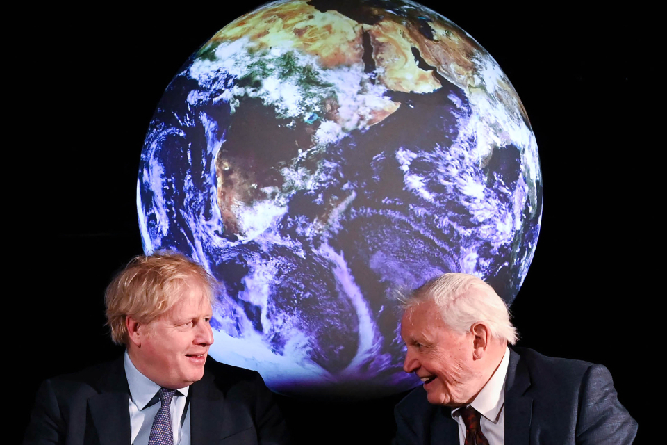 Prime Minister Boris Johnson and Sir David Attenborough sitting against a backdrop with an image of the globe